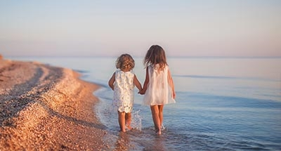 Two children walking on the beach