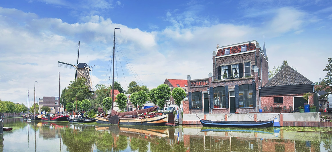 Boats on the canal front and windmill, Gouda